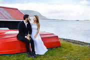 Young bride and groom talking on bank of northern lake