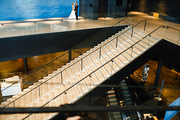 Staircase and escalator inside modern building with newlyweds on top floor