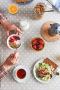 Directly above view of served table for breakfast with cup of herbal tea, fresh juicy strawberries, colorful salad and bowl with corn flakes, milk and berries, unrecognizable man ready to eat