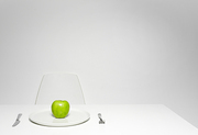 Dieting concept: lone fresh green apple on plate served for one in white room