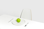 Dieting concept: ripe fresh green apple on plate served for one in empty white room