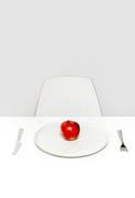 Healthy eating concept: ripe fresh red apple on plate served for one in empty white room