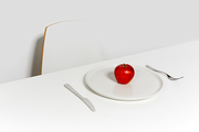 Diet concept: ripe fresh red apple on plate served for one in empty white room