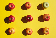Directly above view of ripe red apples arranged in rows, with one green apple standing out,  on bright yellow background, healthy eating concept