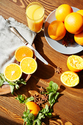 Directly above view of rustic wooden table with fruits and spices on it, all set for making exotic lemonade: fresh ripe oranges cut in half, mint and star anise scattered in elegant assortment lit by sunlight