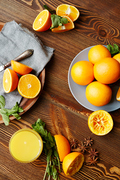 Directly above view of rustic wooden kitchen table with fruits and spices laid out on it, all set for squeezing fresh juice: delicious ripe oranges cut in half, mint and star anise scattered in elegant assortment