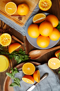 Directly above view of rustic kitchen table with fruits and spices on It: delicious ripe oranges cut in half, mint and star anise scattered in elegant assortment  with wooden cutlery