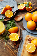Rustic kitchen table with homegrown fruits and spices on It: delicious ripe oranges cut in half, mint, cinnamon and star anise scattered in elegant assortment with wooden cutlery
