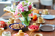 Rustic wooden table covered with bowls of freshly collected gooseberries and raspberries, bouquet of field flowers, homemade pies and cups of tea