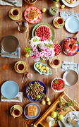 Top view of fresh berries, homemade waffles, ripe fruits, plates and cups of tea on rustic wooden background
