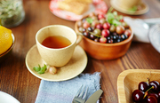 Cup of scented herbal tea on plate and bowls of ripe gooseberries and cherries on wooden background, close-up view