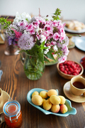 Still life of fresh-cut field flowers in vase, ripe apricots and raspberries from garden and cup of tea placed on dark wooden table