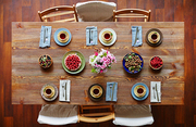Directly above view of table covered with fresh garden berries, homemade pastry, flowers and tea set for six people