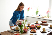 Young pretty woman setting table with delicious homemade desserts, garden fruits and berries, field flowers and tea cups