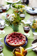 Tasty dessert among fresh flowers, homemade drink and red wine on festive table
