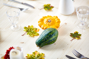 Ripe cucurbits among served festive table decorated with autumn leaves