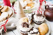 Appetizing cupcakes with whipped cream and chocolate sprinkles on top, pieces of cake, fresh croissant on plate surrounded by other desserts and homemade pastry