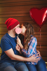Amorous dates with heart-shaped candy and balloon kissing in embrace