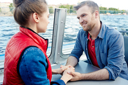 Young sweethearts having love talk on board of steamer during romantic voyage