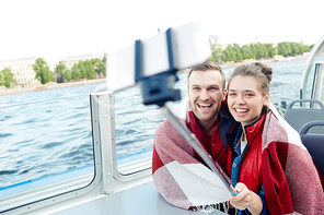 Couple with selfie-stick photographing on cruise tour