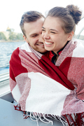 Joyful couple in embrace wrapped in plaid