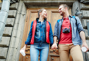 Cheerful sweethearts standing by door of architectural place