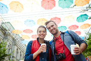 Adventurous tourists with drinks in umbrella alley