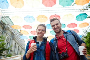 Sweethearts with drinks standing under colorful umbrella sky