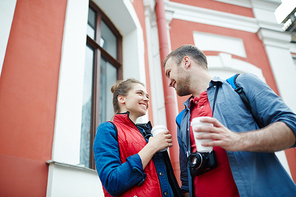 Young man and woman with hot drinks spending leisure in urban environment