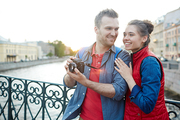 Young amorous adventurers shooting sights of foreign city during journey
