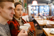 Young couple with cups of tea relaxing in cafeteria