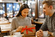 Happy young woman opening gift-box with surprise for valentine day