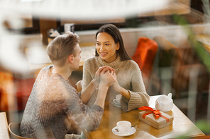 Amorous girl and guy looking at one another while sitting by table in cafe
