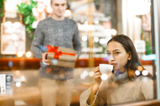 Young amorous man going to make surprise for his girlfriend while she having tea in cafe