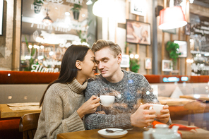 Young affectionate couple relaxing in cafe by cup of coffee