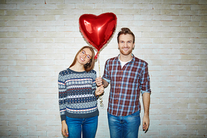 Happy couple holding symbol of love - red heart-shaped balloon
