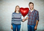 Romantic young couple holding red balloon in form of heart