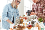Talented food stylist and photographer gathered together at modern production studio with panoramic windows and making preparations for commercial photoshoot