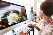 Designer sitting in front of computer monitor and retouching images