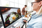 Professional food designer sitting in front of computer monitor in production studio