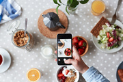 Unrecognizable food blogger taking picture of appetizing breakfast with help of mobile phone, focus on foreground