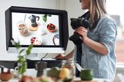 Young food photographer looking at new shot on display of monitor