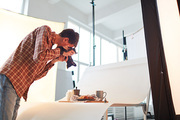 Young photographer shooting food composition on table in production studio