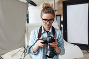 Woman with photocamera working in studio