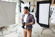 Portrait of smiling bearded photographer wearing checked shirt and baseball cap looking away while taking short break from work, interior of spacious photostudio on background