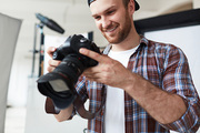 Enthusiastic bearded photographer taking picture with help of professional camera while standing at spacious photostudio