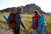 Happy young couple traveling together in mountains: man and woman looking at each other holding hands on hiking path on sunny day