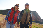 Portrait of smiling young couple wearing active clothes smiling brightly walking on hiking path in mountains together holding hands on sunny day