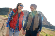 Young man and woman exploring wild nature, standing together on hiking path laughing and holding hands on sunny day in mountains