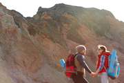 Couple of young travelers, man and woman, hiking in wild nature, man and woman wearing tourist gear with big backpacks standing holding hands against backgrounds of enormous mountain, wide shot with copy space
